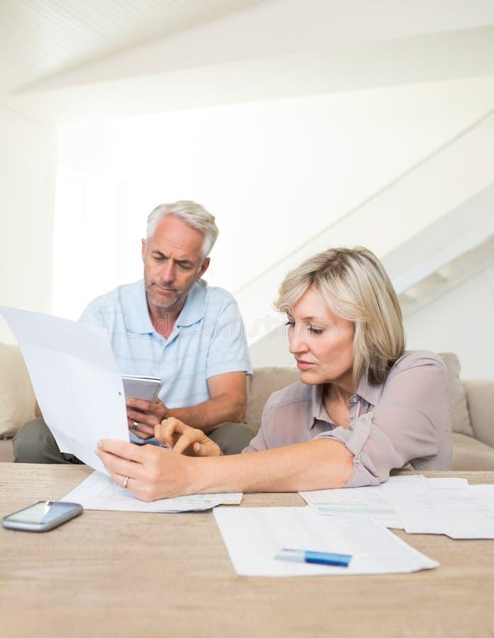 Skoncentrowany dorośleć pary z rachunkami w domu zdjęcia stock