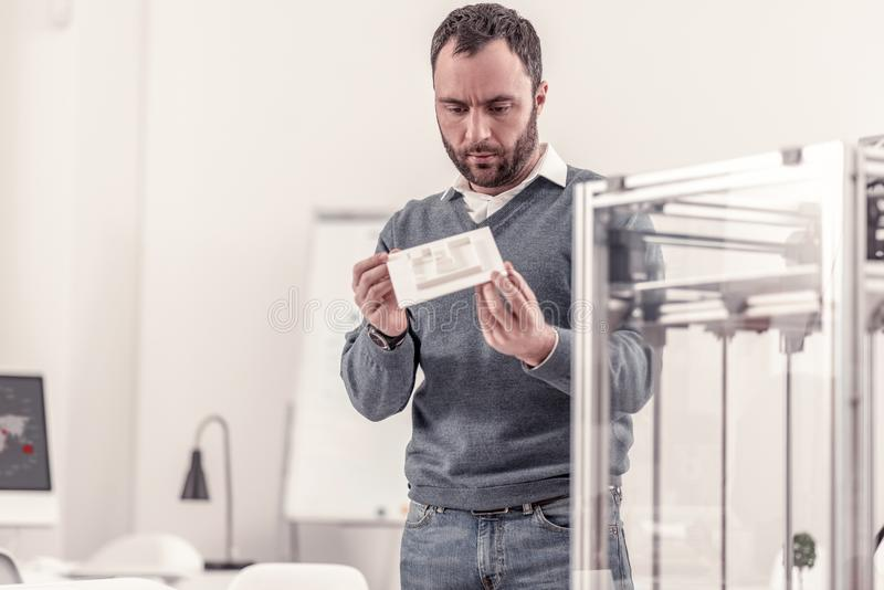 Skoncentrowany dorosły mężczyzna trzyma szczegółu 3d drukarka obraz stock