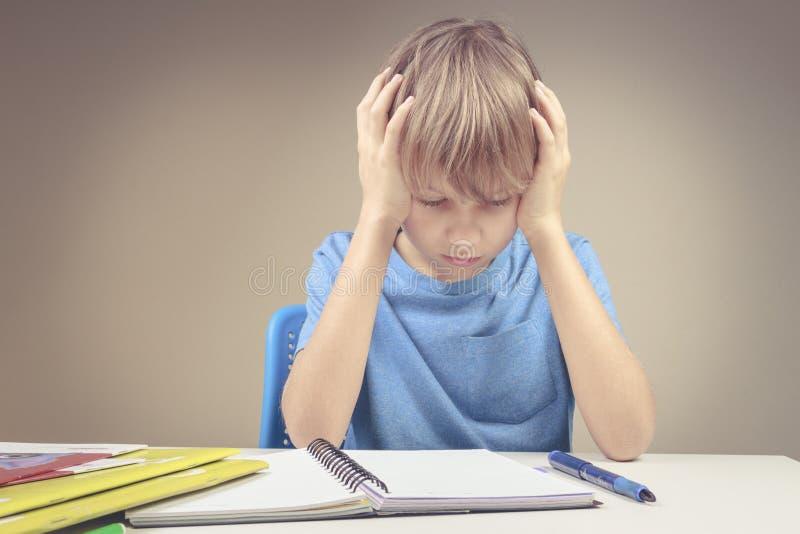 Skoncentrowany dziecko robi jego pracie domowej w domu Chłopiec obsiadanie i patrzeć wewnątrz książki i notatniki zdjęcia royalty free