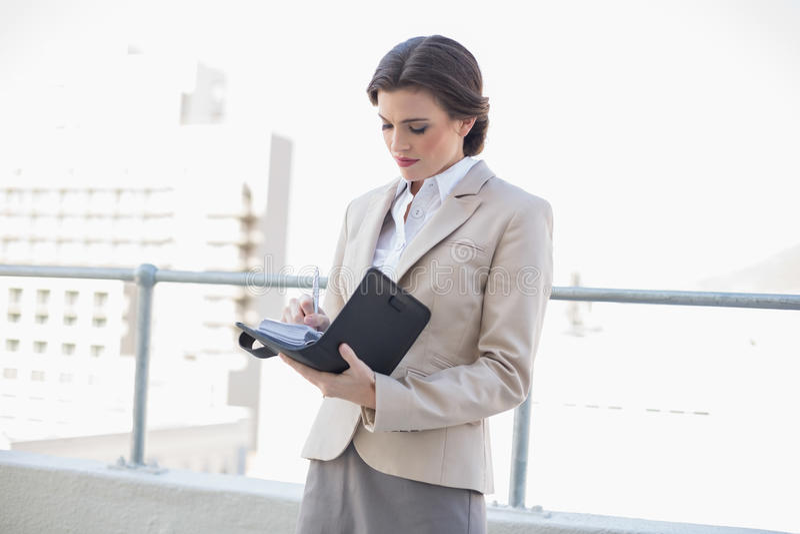 Skoncentrowany elegancki brown z włosami bizneswoman wypełnia jej rozkład fotografia royalty free