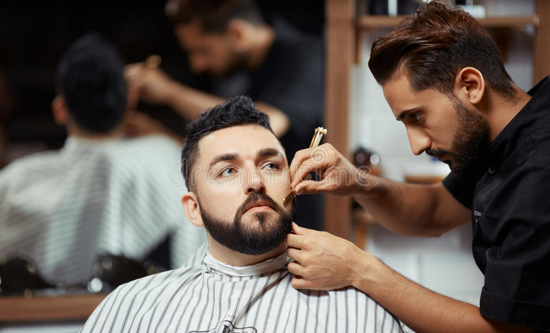 Skoncentrowany fryzjer męski pracuje z mężczyzna obrazy stock