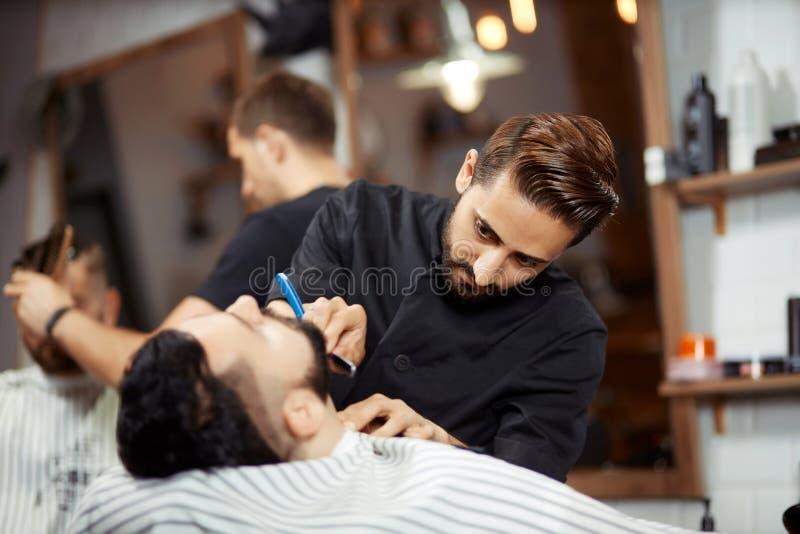 Skoncentrowany fryzjera męskiego golenia młody człowiek obraz royalty free
