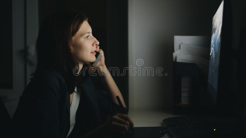 Skoncentrowany kobieta projektant opowiada telefon pracuje w biurze przy nocą używać komputer i grafiki pastylkę kończyć pracę fotografia stock