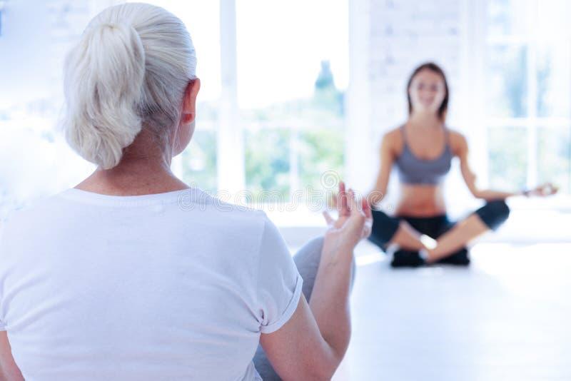 Skoncentrowany kobiety obsiadanie w joga pozyci fotografia royalty free