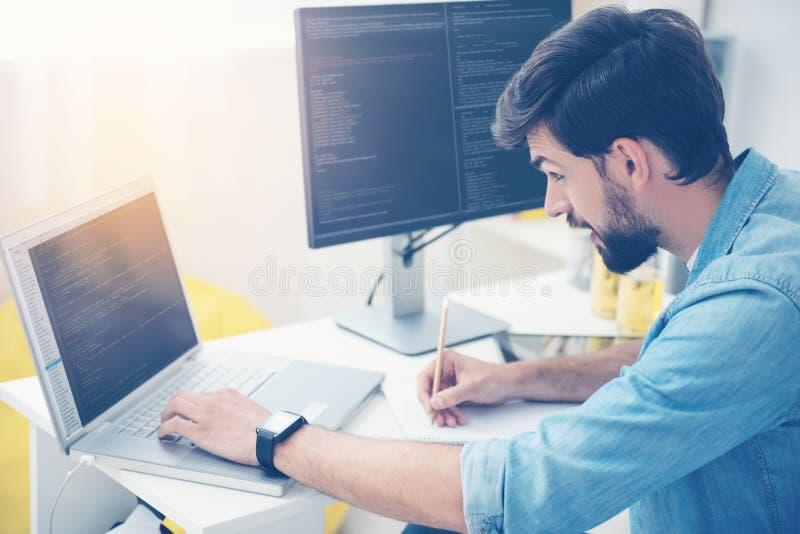 Skoncentrowany mężczyzna cyfrowanie na laptopie zdjęcia royalty free