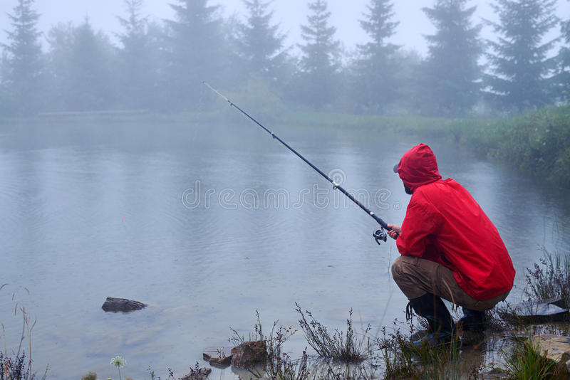 Skoncentrowany mężczyzna obsiadanie, połów na jeziorze i fotografia stock