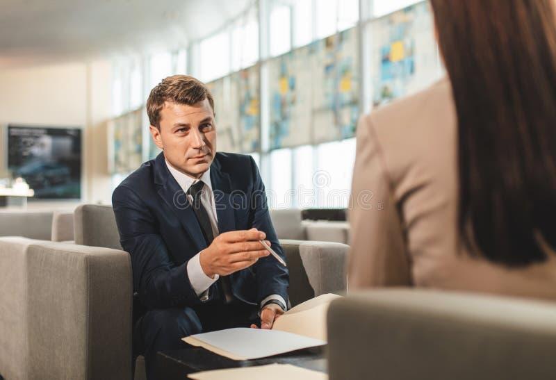 Skoncentrowany mężczyzna obsiadanie przed żeńskim kolegą zdjęcia stock