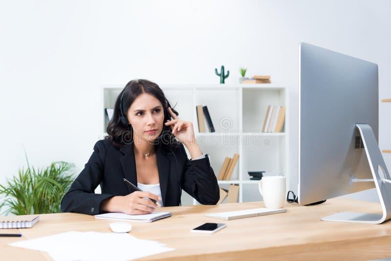 skoncentrowany młody żeński centrum telefoniczne pracownik z słuchawki obraz stock