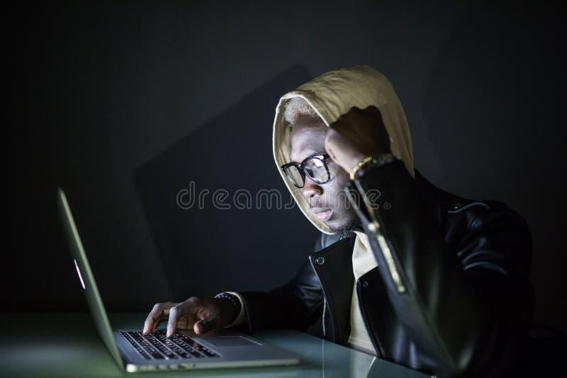 Skoncentrowany młody afro amerykański hackera używać komputerowy i kraść informację w ciemnym pokoju obrazy royalty free