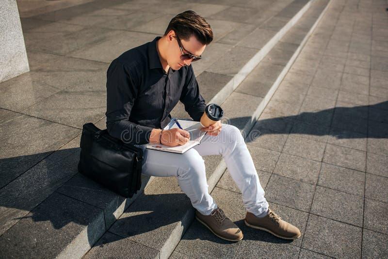 Skoncentrowany młody człowiek siedzi na krokach na ulicie i pisze w notatniku Trzyma filiżanka kawy w ręce Faceta spojrzenie zdjęcia royalty free
