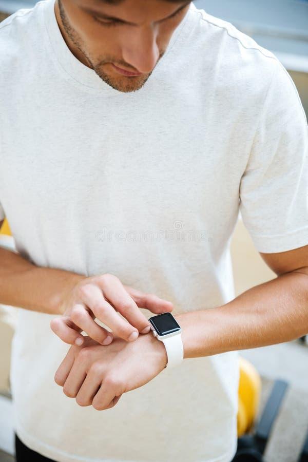 Skoncentrowany młody sporta mężczyzna patrzeje zegarek zdjęcie royalty free