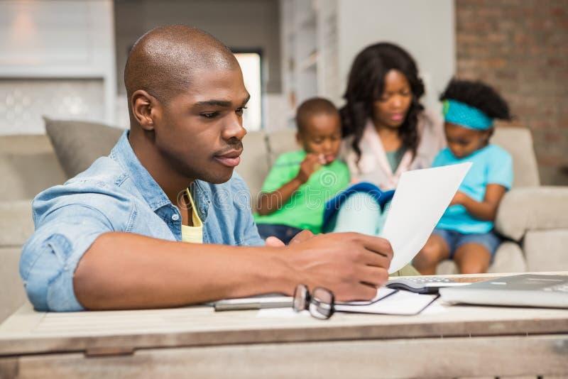Skoncentrowany ojca czytania papier obrazy royalty free