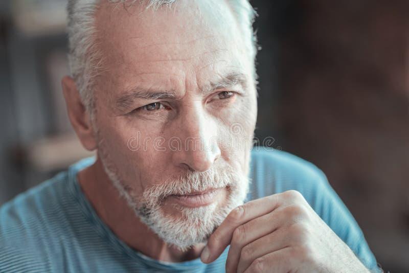 Skoncentrowany poważny mężczyzna patrzeje na boku i myśleć obraz royalty free