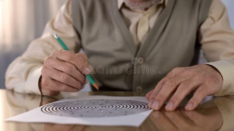 Skoncentrowany przechodzić na emeryturę mężczyzna rozwiązuje logika test przy stołem, pamięci ćwiczenie, neurologia obrazy royalty free
