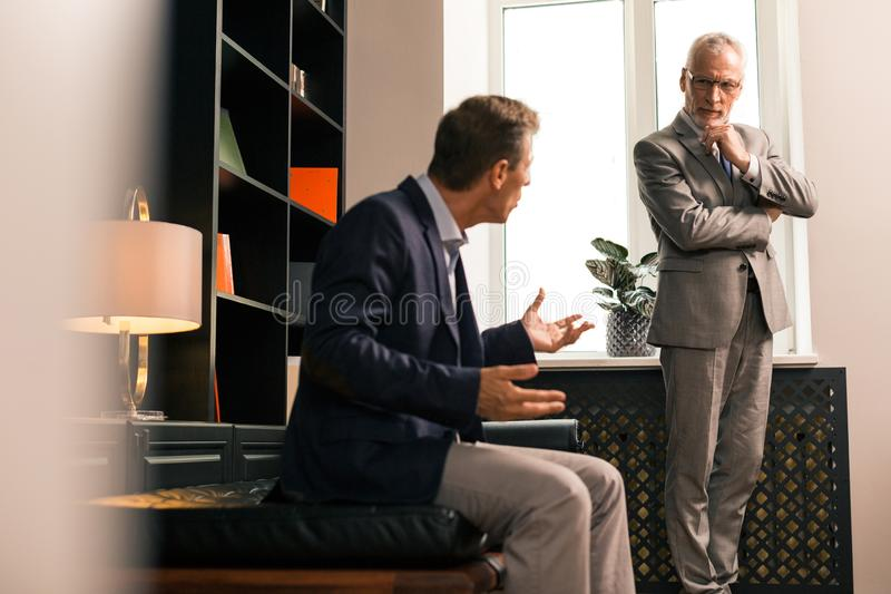 Skoncentrowany starszy psycholog słucha attentively jego pacjent fotografia stock
