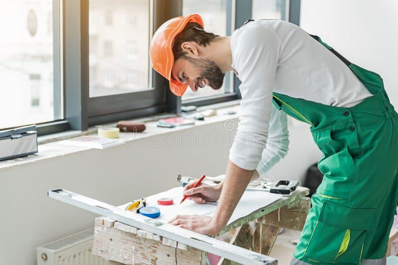 Skoncentrowany uśmiechnięty budowniczy pracuje na planie zdjęcia royalty free