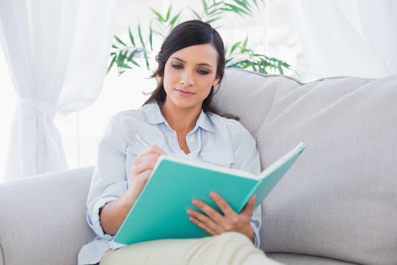 Skoncentrowany wspaniały brunetki writing podczas gdy siedzący na kanapie zdjęcie royalty free