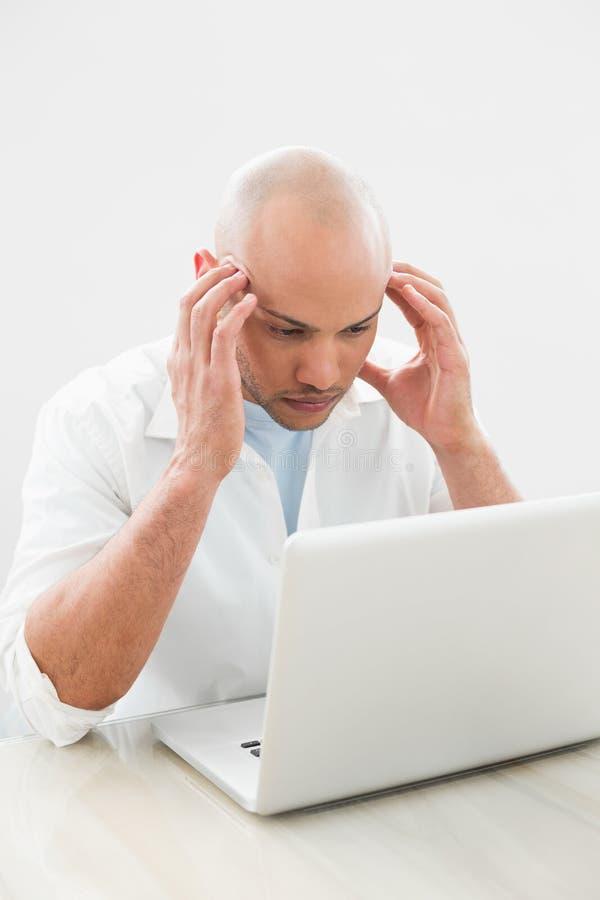 Skoncentrowany zmartwiony przypadkowy mężczyzna używa laptop przy biurkiem zdjęcie royalty free
