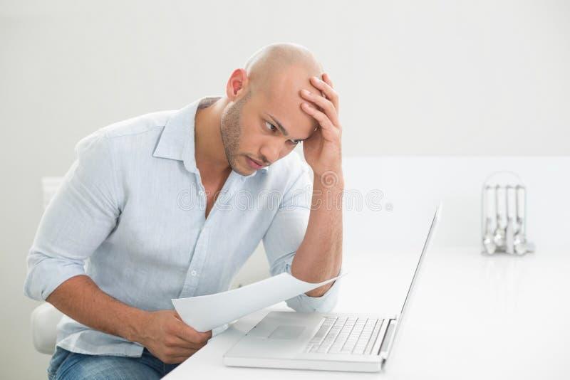Skoncentrowany zmartwiony przypadkowy mężczyzna używa laptop w domu obrazy royalty free