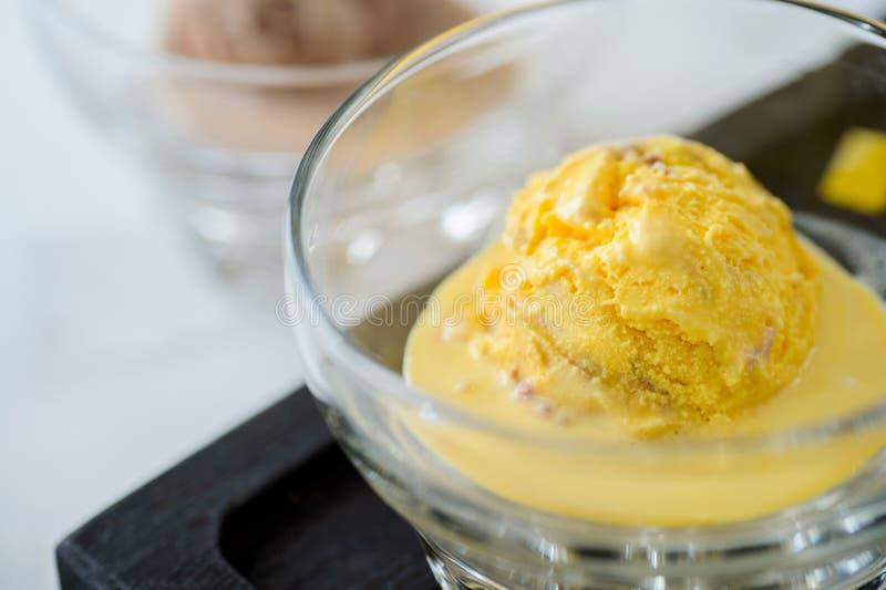 Skopa av gul glass i en bunke royaltyfri fotografi
