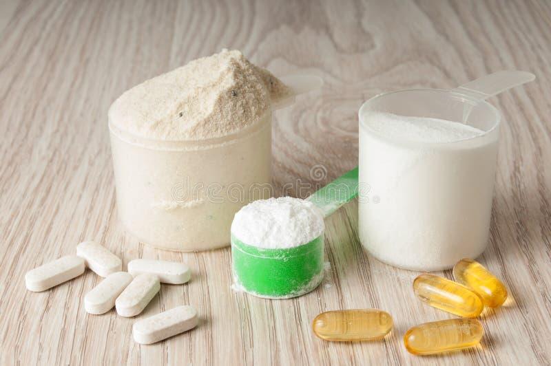 Skopa av protein, bcaa och creatine, omega3 i preventivpillerar royaltyfri bild
