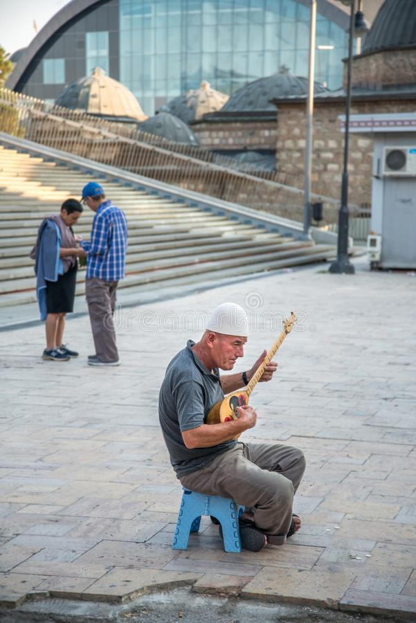 SKOPJE, 29,2018 MACEDONIË-AUGUSTUS: de mens speelt muziek op een traditioneel snaarinstrument stock fotografie