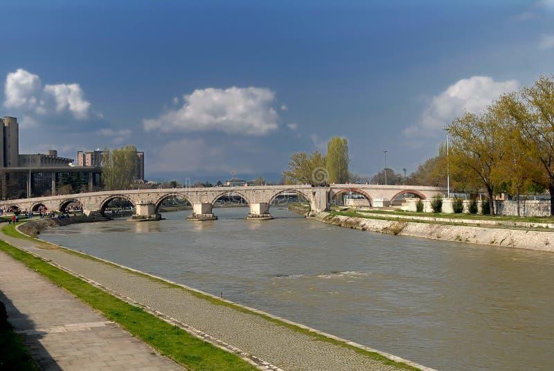SKOPJE, MACEDONIA - 1° APRILE 2007: La gente che cammina il vecchio ponte di pietra sul fiume Vardar al bello sunseth fotografie stock