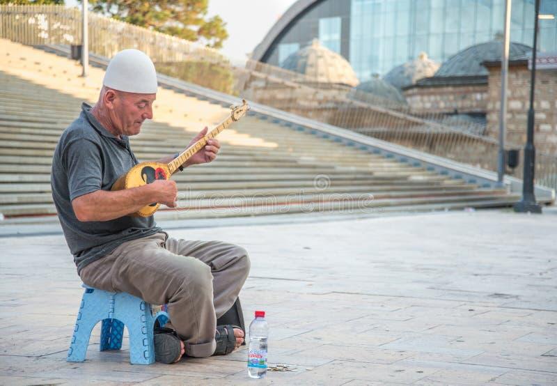 SKOPJE, MACEDONIA-AUGUST 29,2018: Mann, der traditionelles albanisches Instrument spielend busking ist lizenzfreies stockbild