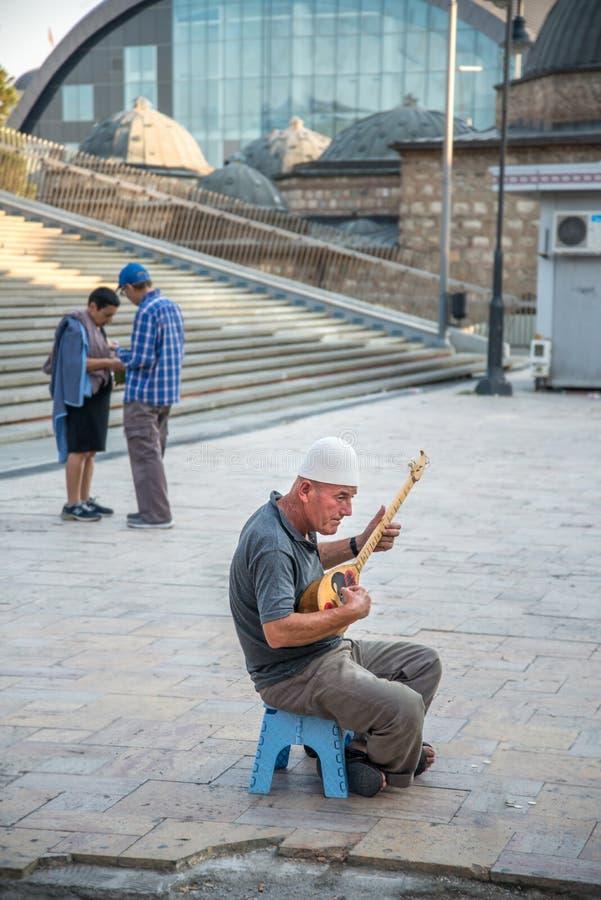 SKOPJE MACEDONIA-AUGUST 29,2018: mannen spelar musik på en traditionell stränginstrument arkivbild
