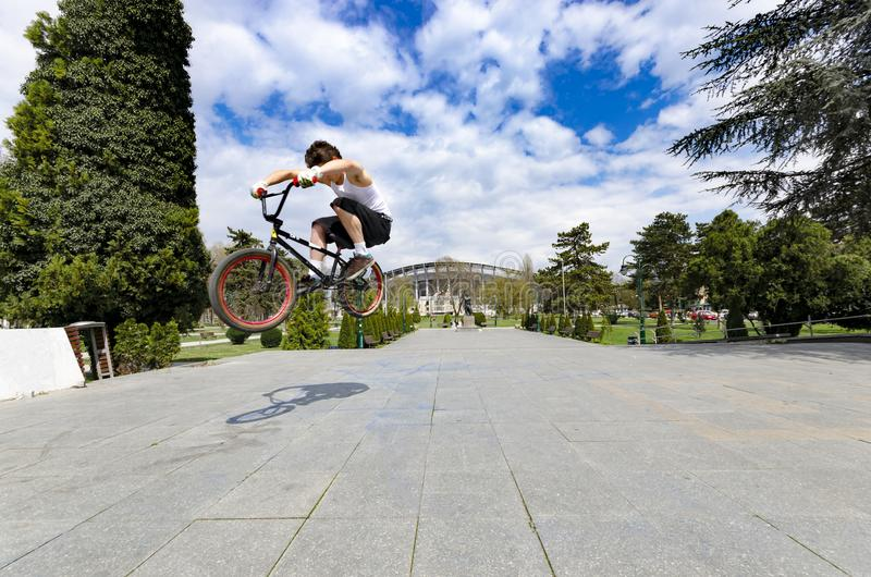 Low view of skillful cyclist jumping high up against sky royalty free stock image