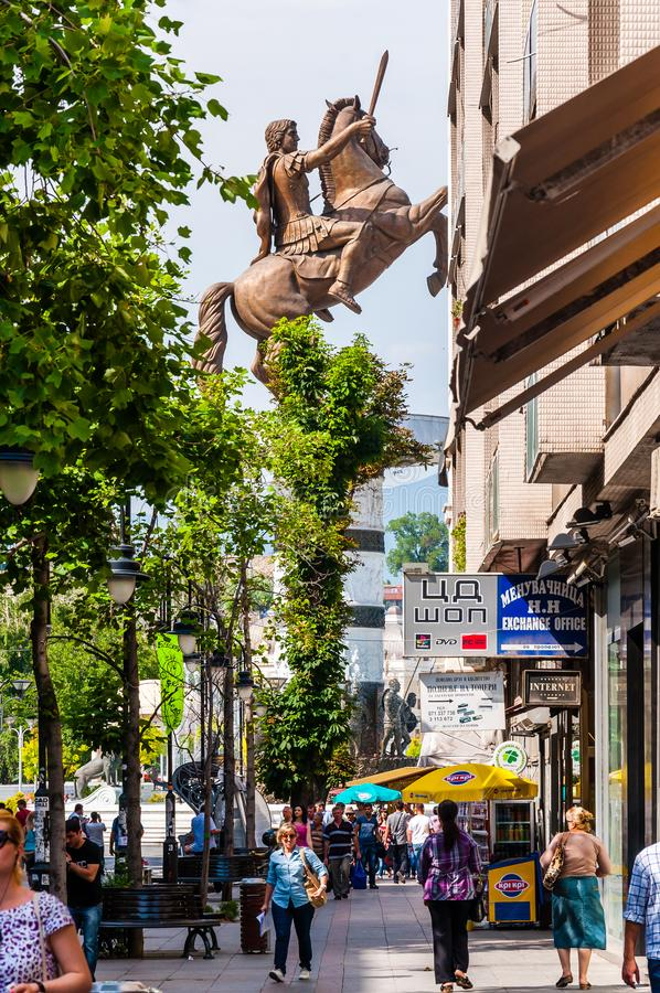 City street view on a giant bronze statue of Alexander the Great at Macedonian Square behind the trees. People, tourists and stock photos