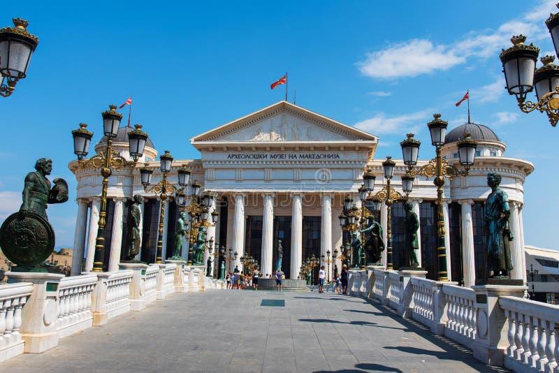 Skopje Makedonien - Augusti 26, 2017: Skopje arkeologiskt museum med stenbron med många monument över den Vardar floden royaltyfri fotografi