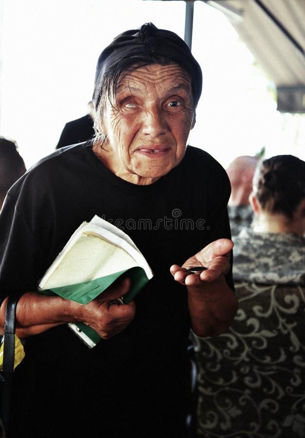 SKOPJE MAKEDONIEN - JUNI 20,2013: Äldre kvinna med ögonproblem som rymmer healtkortet i hans handtiggeri för pengar i a royaltyfri foto