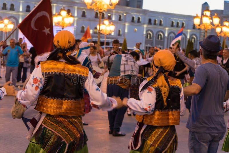 Skopje/Noord-Macedonië - Juni 07 2019: Groep die mensen in folklorekleding dansen in een festival Het traditionele kostuum van Oo stock fotografie