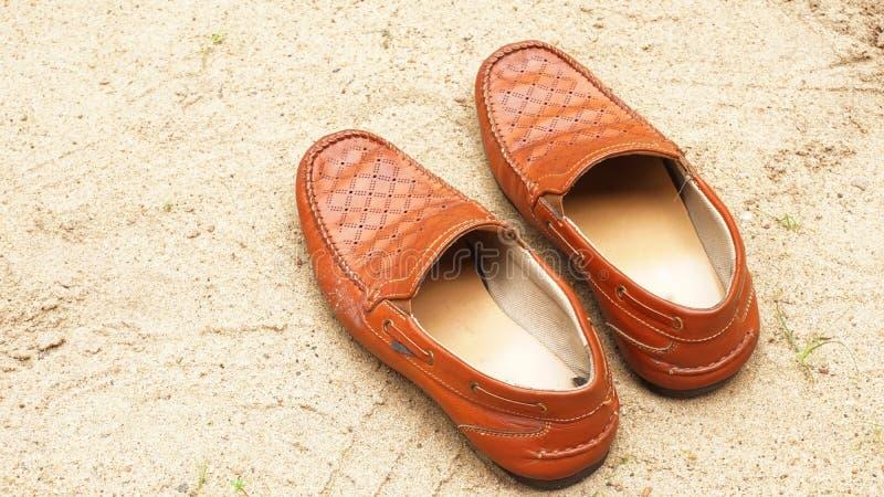 Skor för dagdrivare för färg för brunt för man` s på sandbakgrund royaltyfria bilder