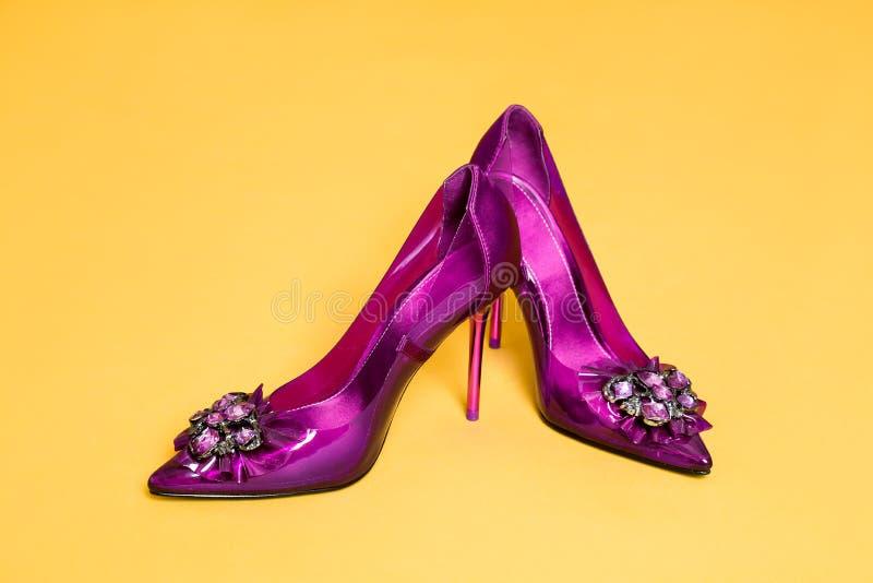 Skor för ` s för eleganta kvinnor med garneringar för hög häl och glamourpå en gul bakgrund arkivfoton