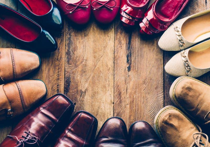 Skor med olika stilar för män och för kvinnor på ett trägolv arkivfoton