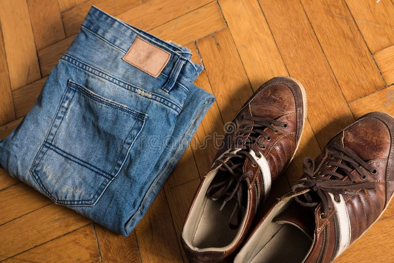Skor och jeans på golvet royaltyfri bild