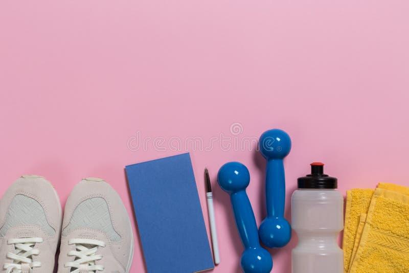 Skor och sportutrustning p? rosa golv arkivbilder