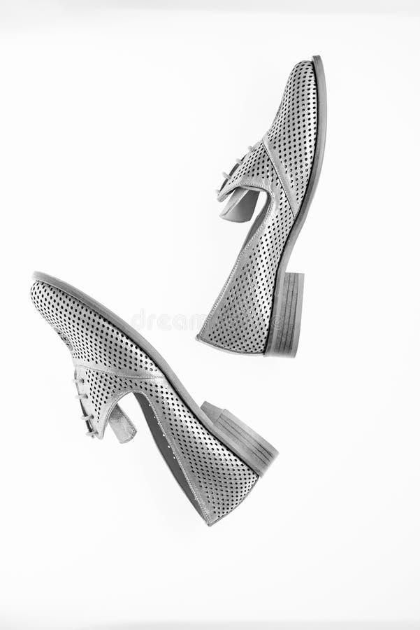 Skor som göras ut ur silverläder på vit bakgrund som isoleras Kvinnligt skodonbegrepp Skodon för kvinnor på den endast lägenheten royaltyfri foto