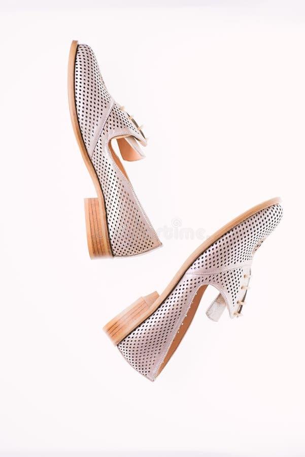 Skor som göras ut ur silverläder på vit bakgrund som isoleras Kvinnligt skodonbegrepp Skodon för kvinnor på den endast lägenheten fotografering för bildbyråer
