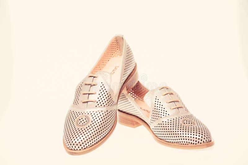 Skor som göras ut ur silverläder på vit bakgrund som isoleras Skodon för kvinnor på lägenheten som är endast med perforering kvin royaltyfria foton