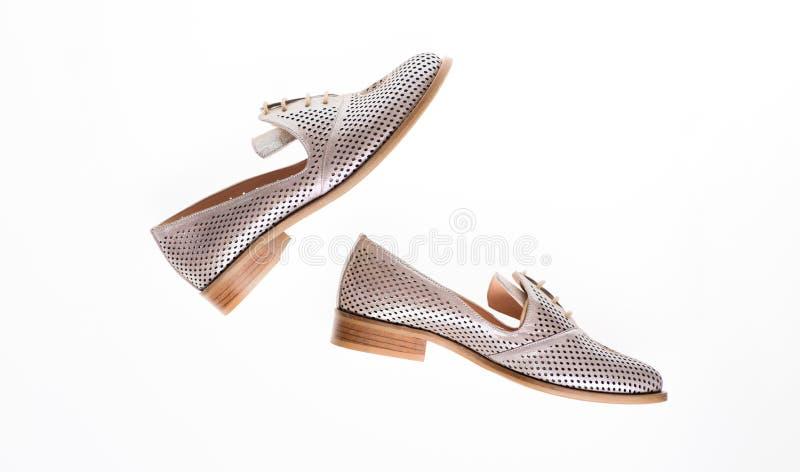Skor som göras ut ur silverläder på vit bakgrund som isoleras Skodon för kvinnor på lägenheten som är endast med perforering par royaltyfri bild