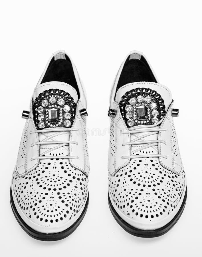Skor som göras ut ur vitt läder på vit bakgrund som isoleras Skodon för kvinnor på lägenheten som är endast med perforering och arkivbild