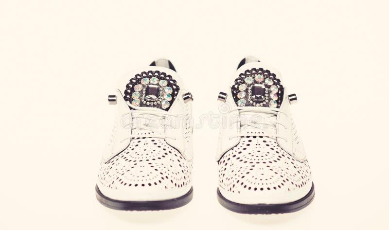 Skor som göras ut ur vitt läder på vit bakgrund som isoleras Skodon för kvinnor på lägenheten som är endast med perforering och fotografering för bildbyråer