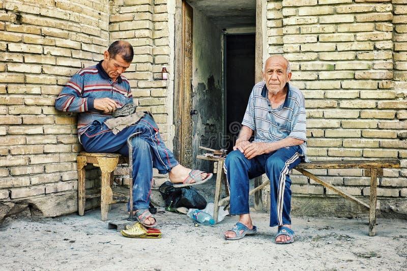 skoreparationsaffären öppnade upp på gatan framme av deras hem i en central asiatisk stil arkivfoto