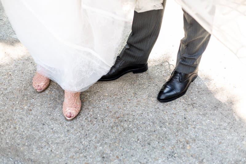 Skorna av en brudgum och en brud som tillsammans står royaltyfri foto