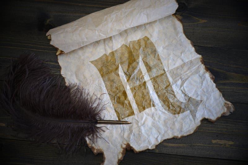 Skorpiontecken av zodiaken på tappningpapper med den gamla pennan på träskrivbordet royaltyfri fotografi