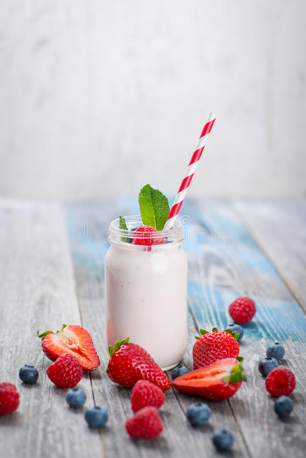 Skorra med att dricka yoghurt, bär och sugrör på trätabellen royaltyfria foton