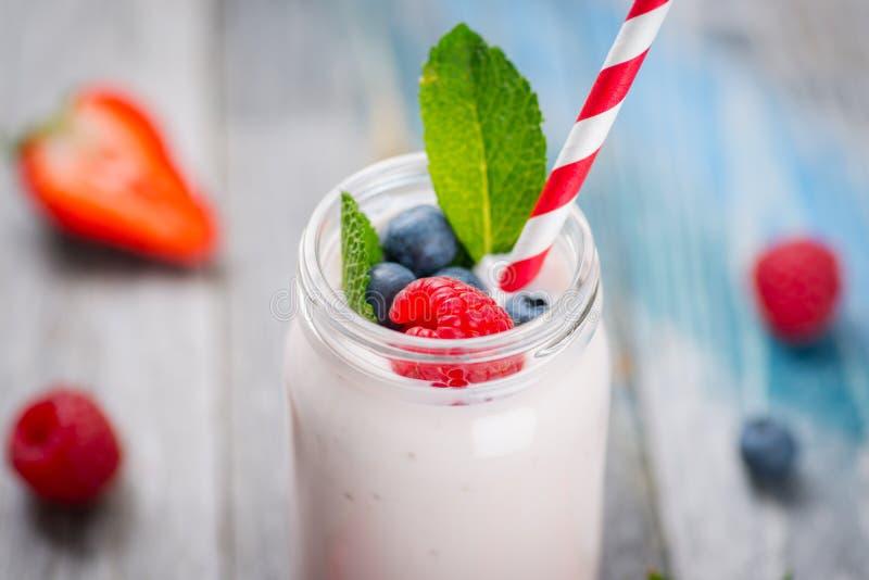 Skorra med att dricka yoghurt, bär och sugrör på trätabellen arkivbilder